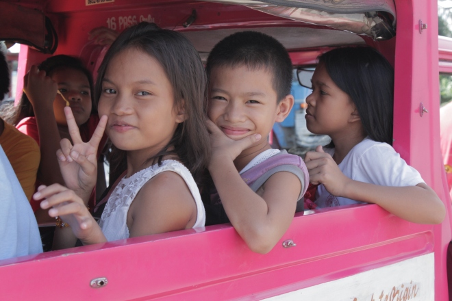 Why yes, that is a bright pink vehicle! Jeepneys are the most popular form of public transportation in the Philippines, and they are also great for hauling loads of ecstatic, screaming, cheering kids. Jeepneys are hot, loud, and uncomfortable, but when it's time to party, a little sweat and discomfort is covered by big, broad smiles from Nicole and Rufo.